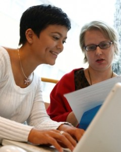 Kaksi naista työskentelee tietokoneen äärellä ja toinen heistä tarkastelee paperia.