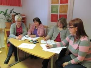 Roolikartan pohtimista, neljä naista työskentelee yhteisen pöydän äärellä.