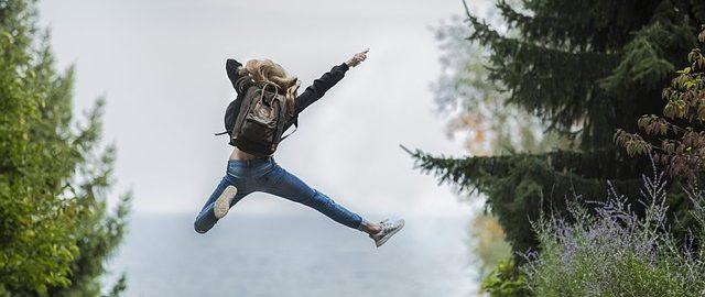 Nuori nainen hyppää ilmaan reppu selässä, taustalla epäselvä merinäköala ja puita.
