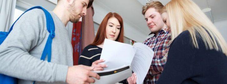 Ohjaamon työntekijöitä ja asiakkaita tarkastelemassa papereita.