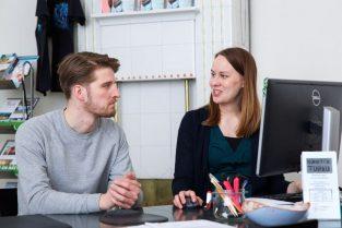 Ohjaustilanne Turun Ohjaamossa, nuori mies kuuntelee tietokoneen äärellä istuvan naisen puhetta.