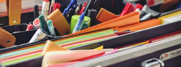 toimistotarvikkeita, kyniä, värikkäitä papereita salkussa