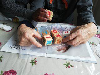 Työssäoppimisjakson kotikäynnillä tutustutaan omaishoidon tehtäviin, kuvassa vanhuksen kädet ja opiskelijan kädet käsittelevät kirjainpalikoita pöydällä.