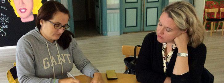 Kaksi naista työskentelee pöydän ääressä Savonlinnan Ohjaamon URAA-valmennuspäivässä.
