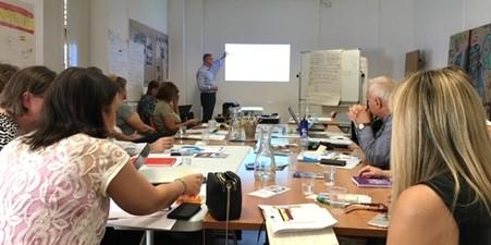 projektissa työskenteleviä henkilöitä kokoushuoneessa pöydän äärellä