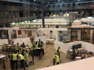 Rakennusalan opetus- ja työtiloja Mansfieldissä Vision Collegessa. Opiskelijat keltaisissa liiveissä työskentelevät seisaallaan pöytien ja työlaitteiden äärellä.