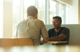 kaksi miestä keskustelee pöydän äärellä
