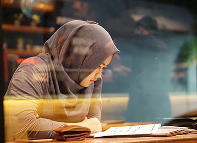 Ikkunan läpi kuvattu huntupäinen näinen lukee pöydällä olevia papereita.