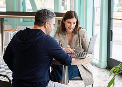 Nainen ja mies, selin kameraan, kahvilan pöydässä katselevat yhteistä kannettavaa tietokonetta.