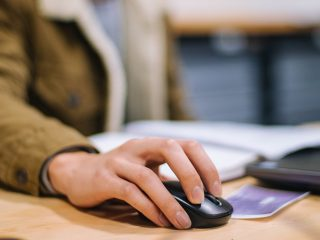 Nuori opiskelija tietokoneen äärellä, lähikuva hiirestä ja kädestä.