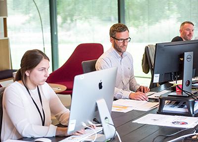 Nuori nainen ja kaksi miestä työskentelevät tietokoneiden äärellä toimistossa.