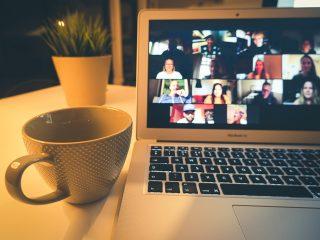 Kannettavan tietokoneen näytöllä verkkokokouksen osallistujia ja tietokoneen vierellä kahvikuppi